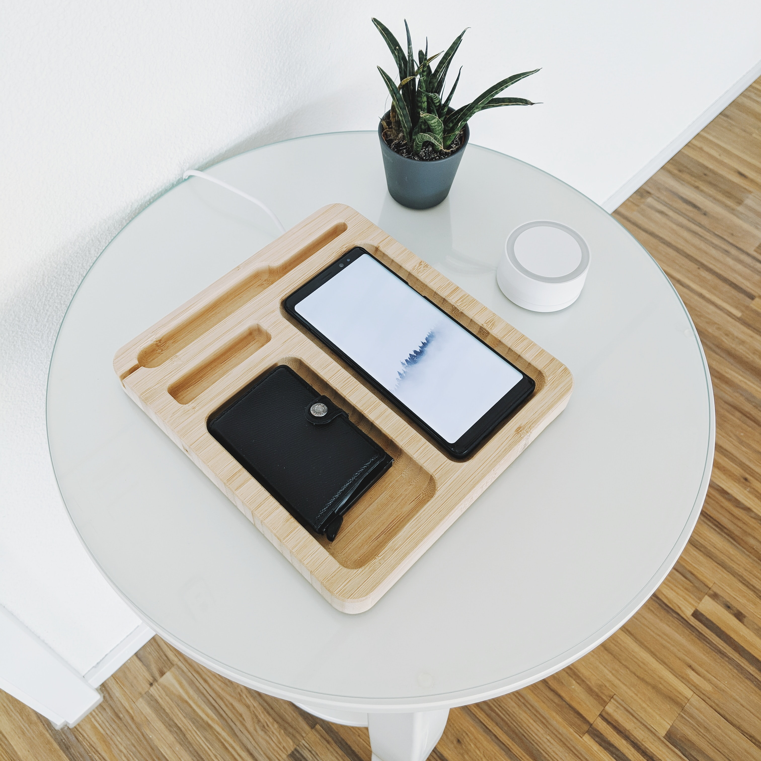 black smartphone with wallet on wooden tray on table