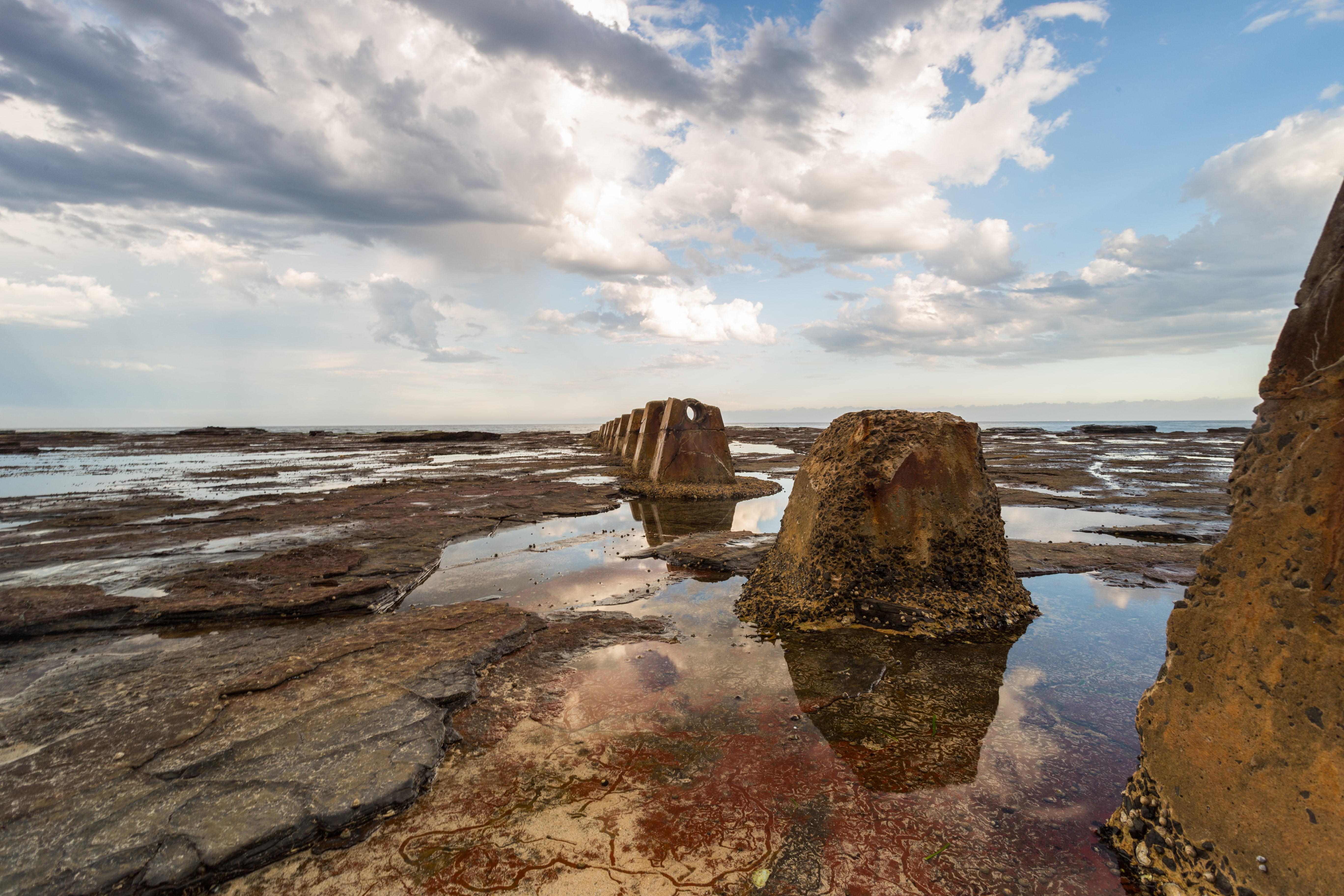 brown rock formation surrounded with water