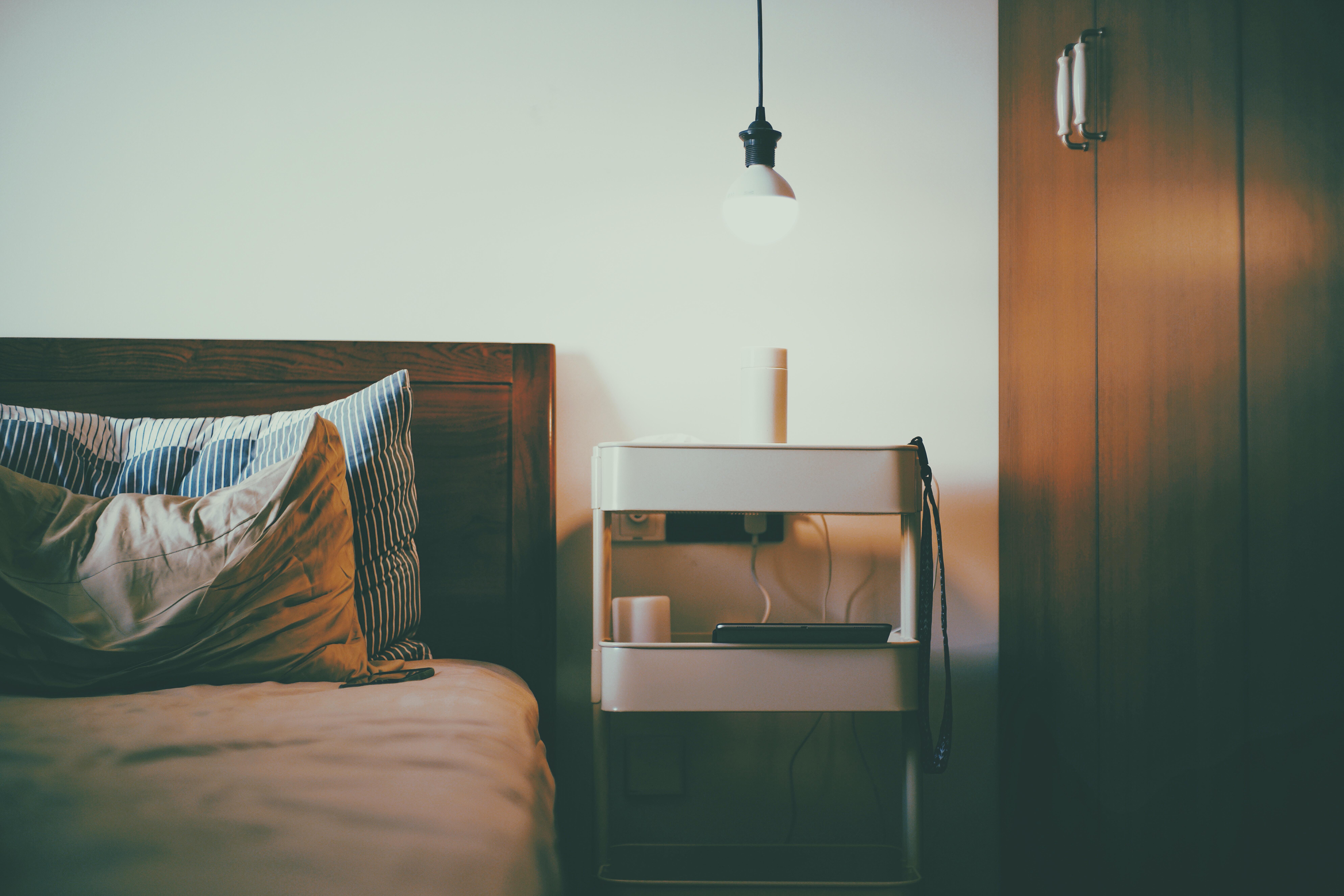 white pendant lamp near bed