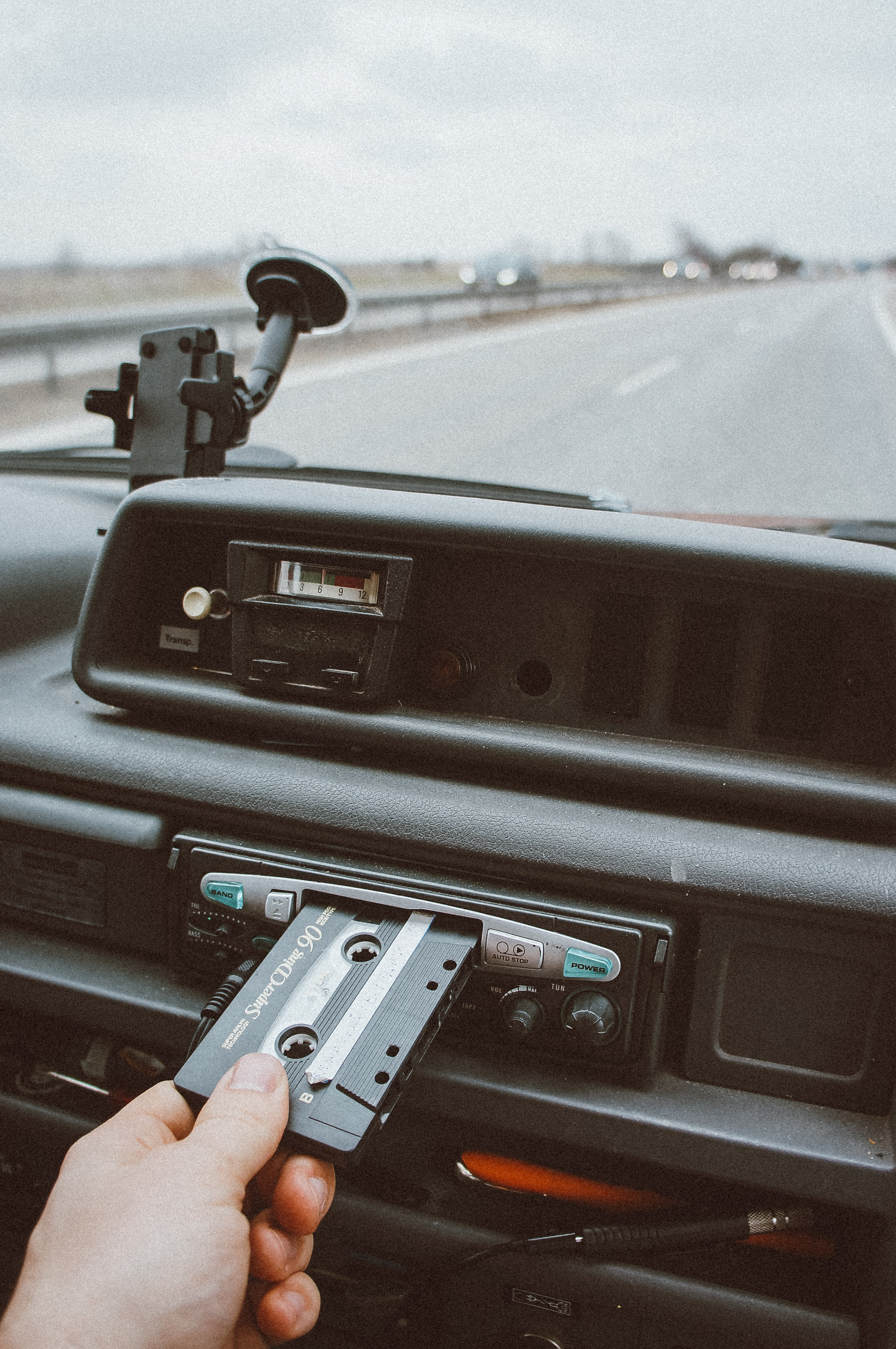 person inserting cassette tape on cassette player