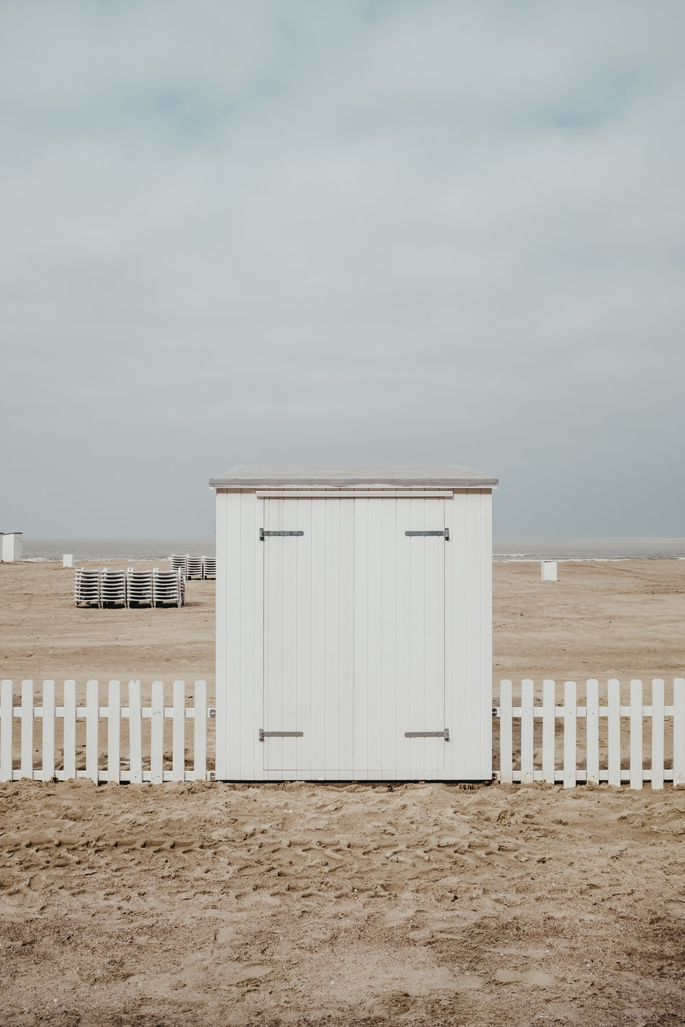 white wooden shed on sand under white clouds