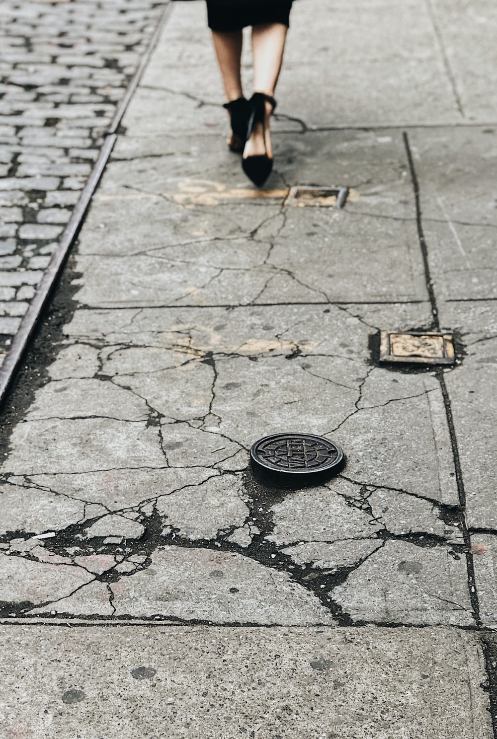 woman in black heeled sandals walking on gray concrete pavement