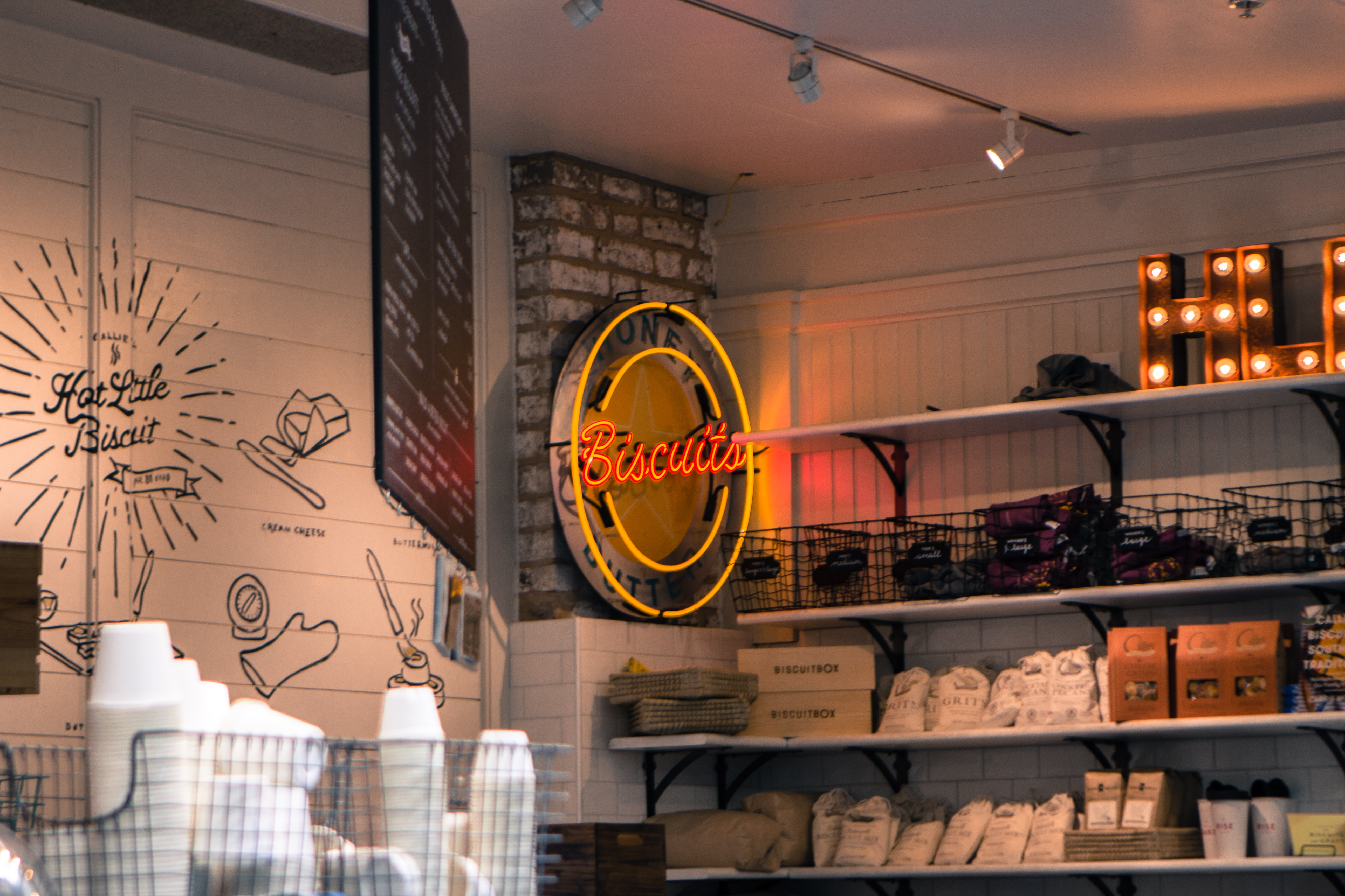 red and yellow Biscuits neon light signage hanged on gray brick wall