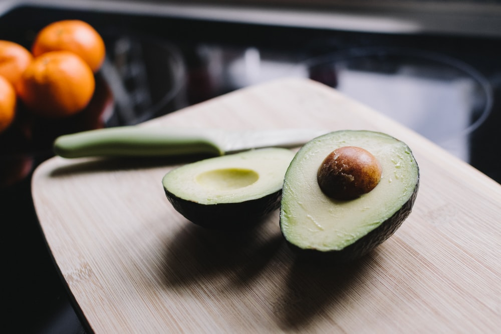 sliced avocado on brown wooden chopping board