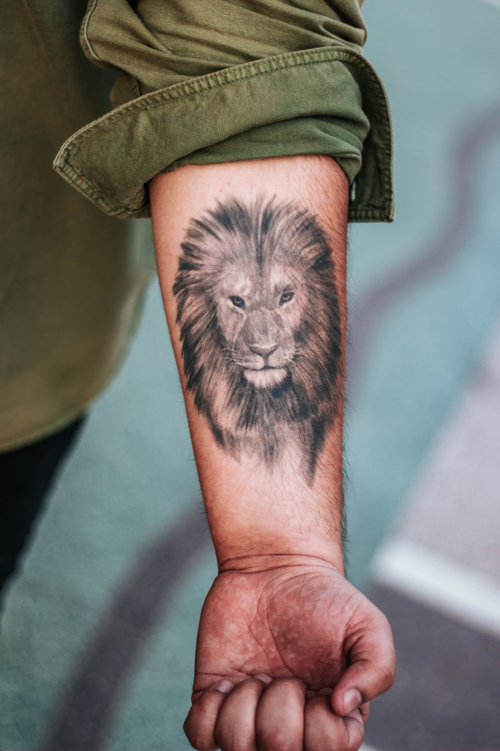 shallow focus photography of lion forearm tattoo