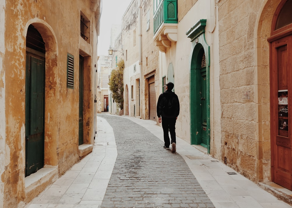 man walking in the middle of the street surrounded by buildings
