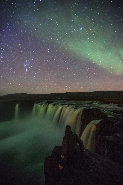 person sitting near waterfalls under aurora lights