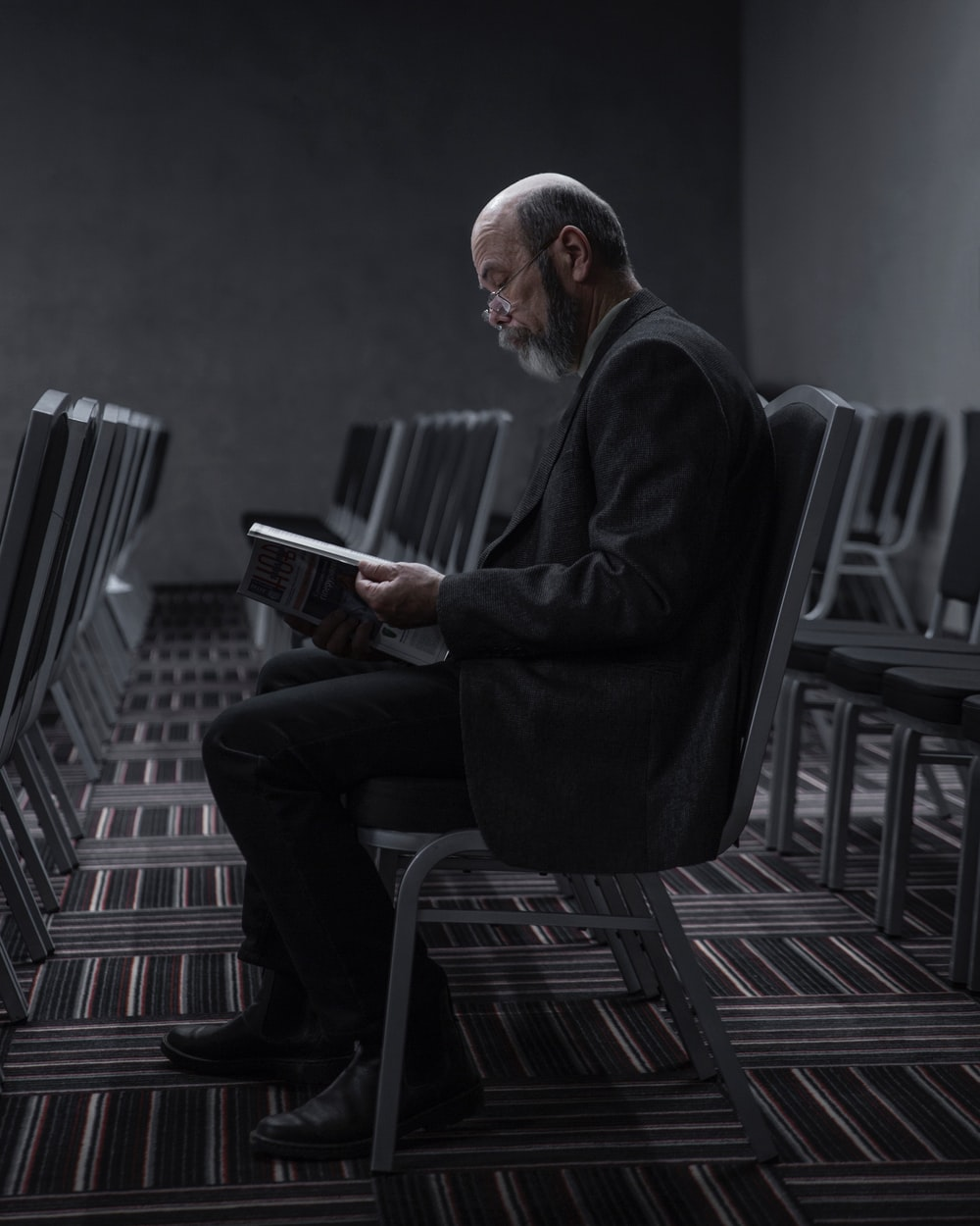 man in black suit sitting on chair