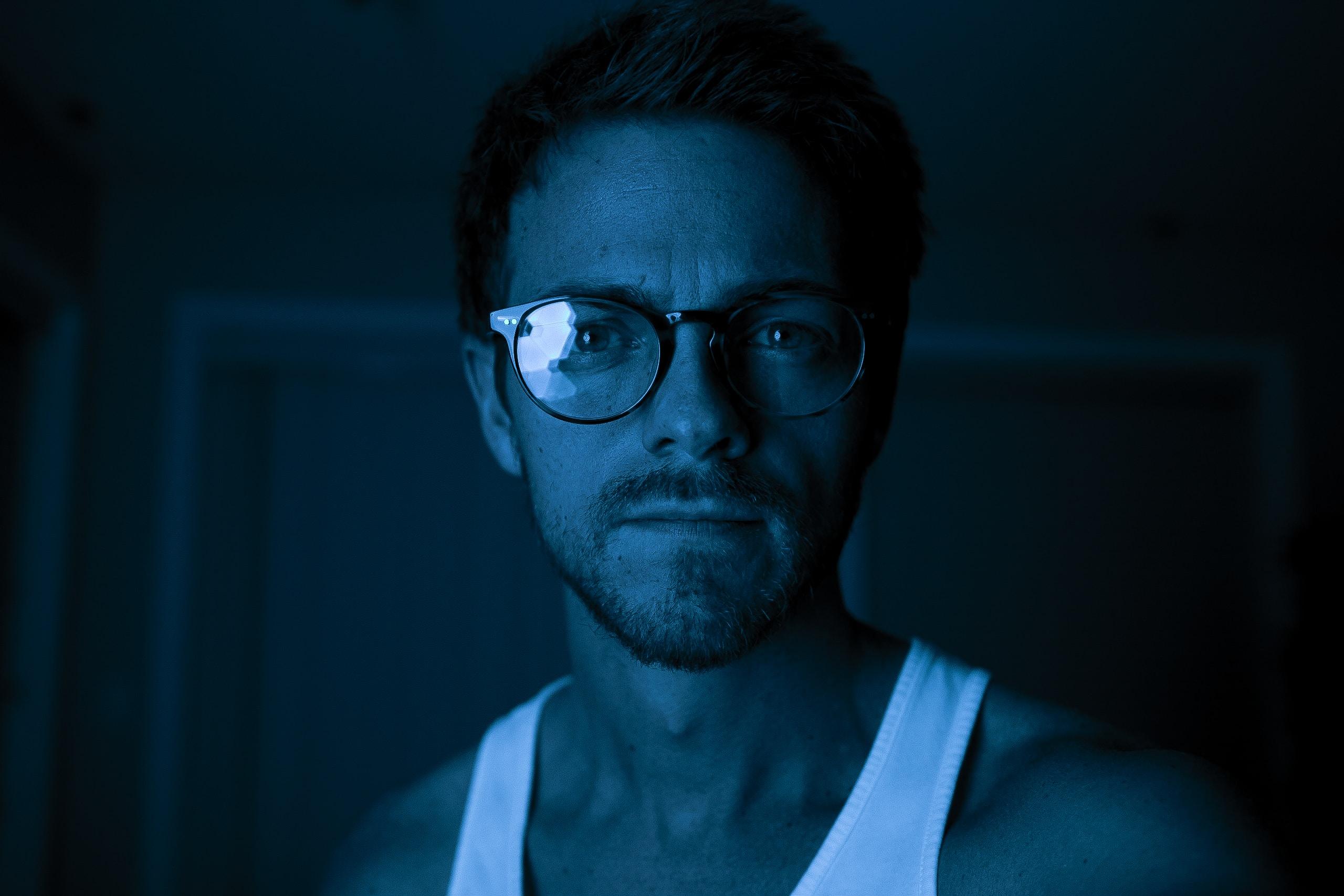 person wearing white top and black framed Wayfarer-style eyeglasses