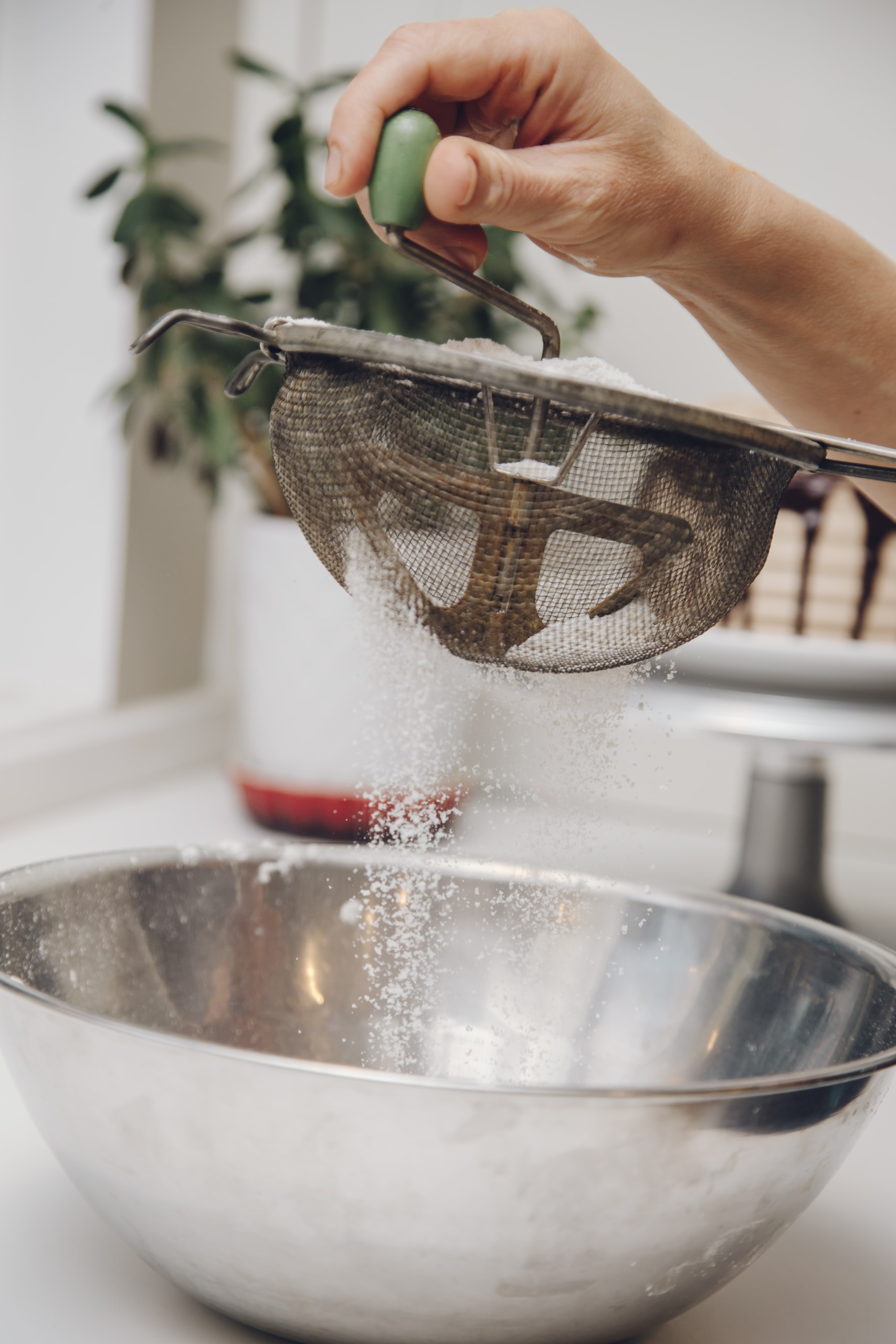 person filtering powder on round stainless steel bowl