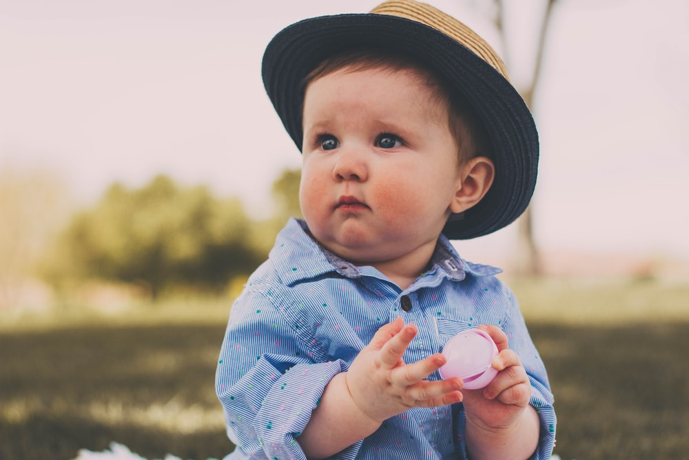 toddler holding ball while sitting
