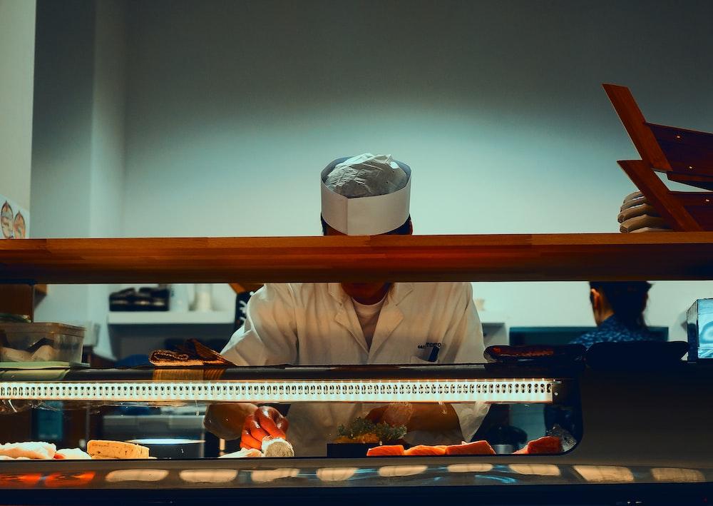 man preparing sushi dish