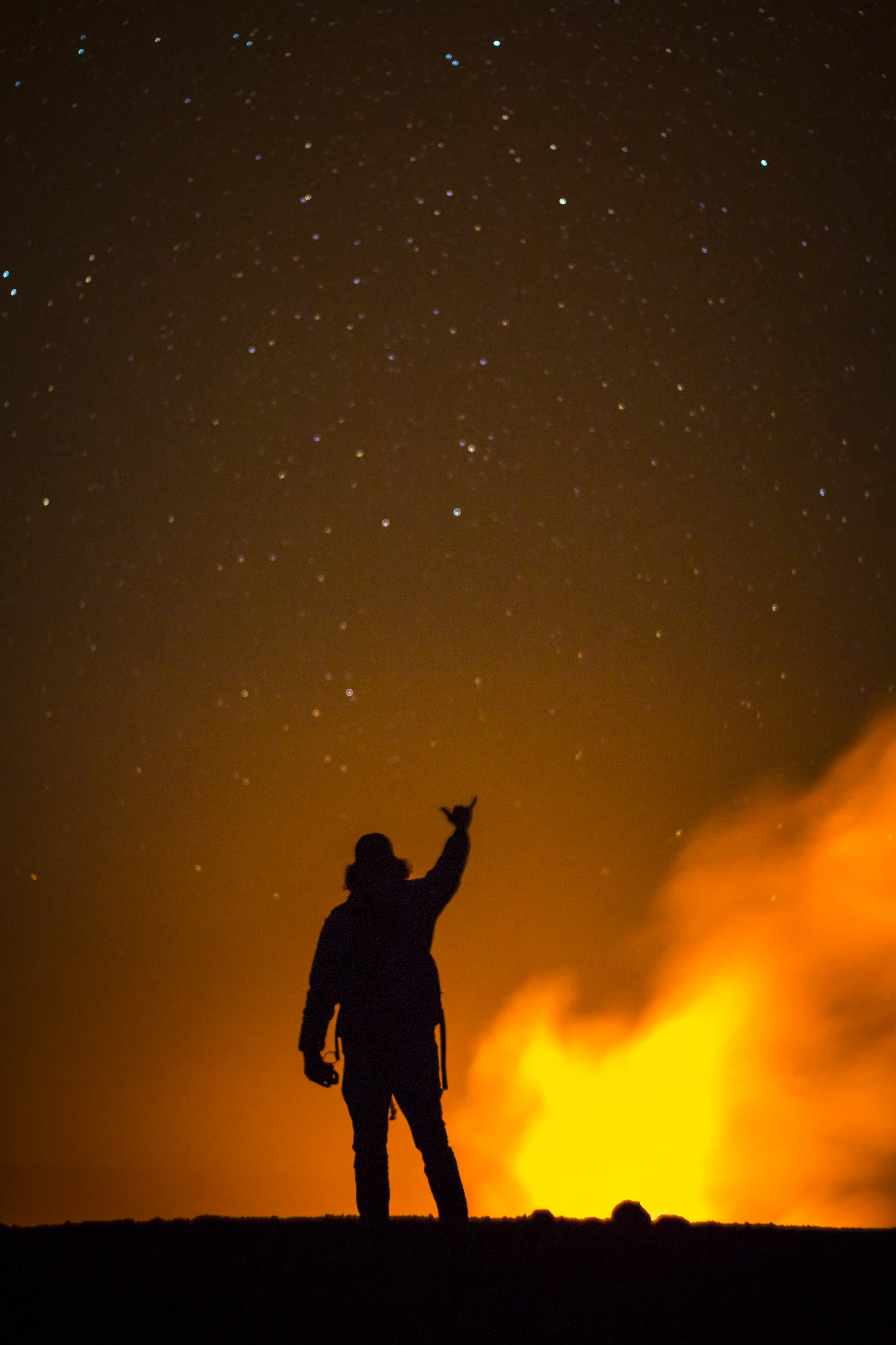 silhouette of man raising right hand
