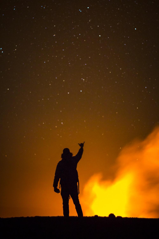 silhouette of man raising right hand