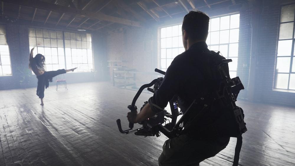 man using video camera shooting woman dancing inside room