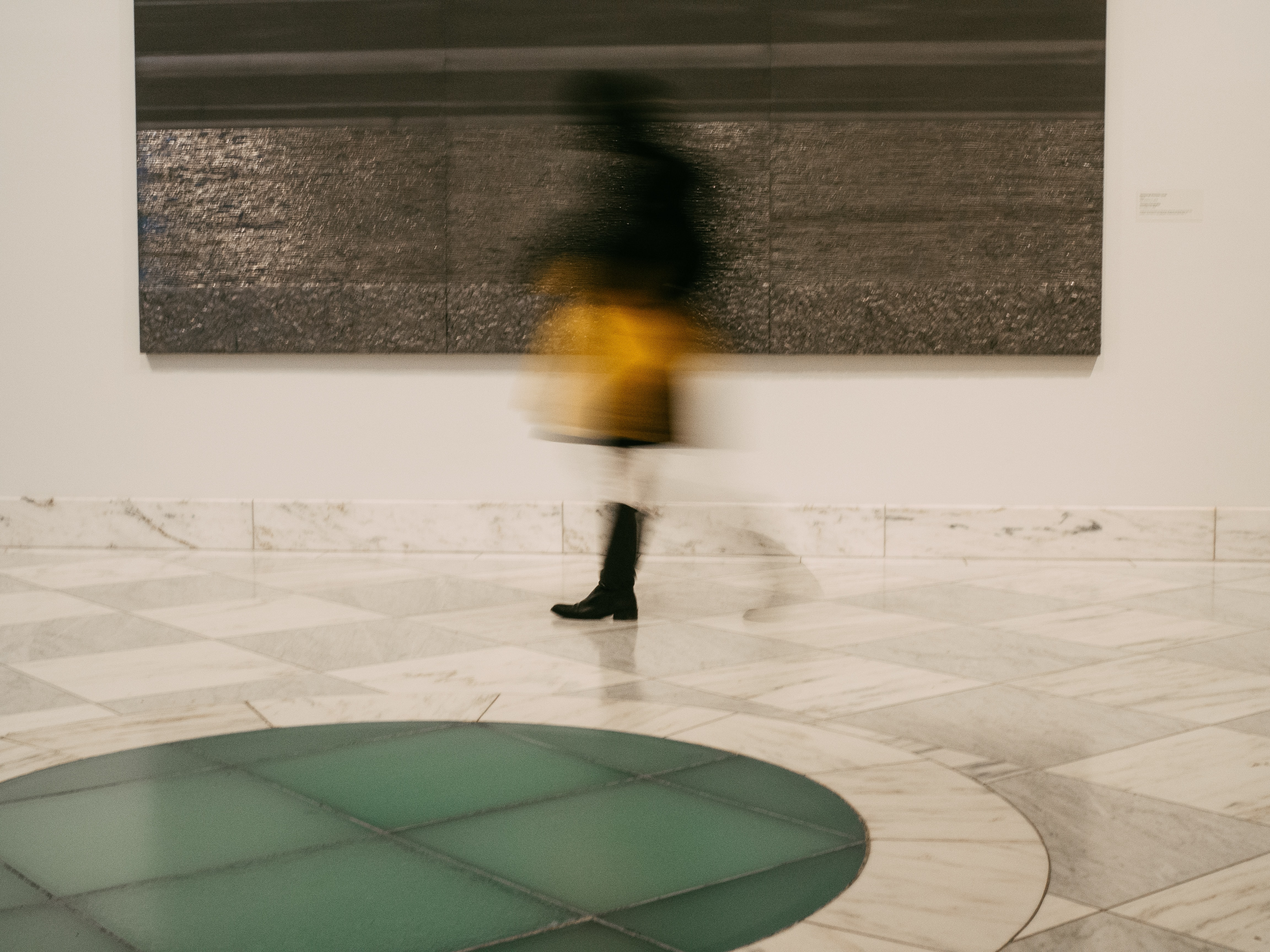 timelapse photography of person walking beside 3-panel painting