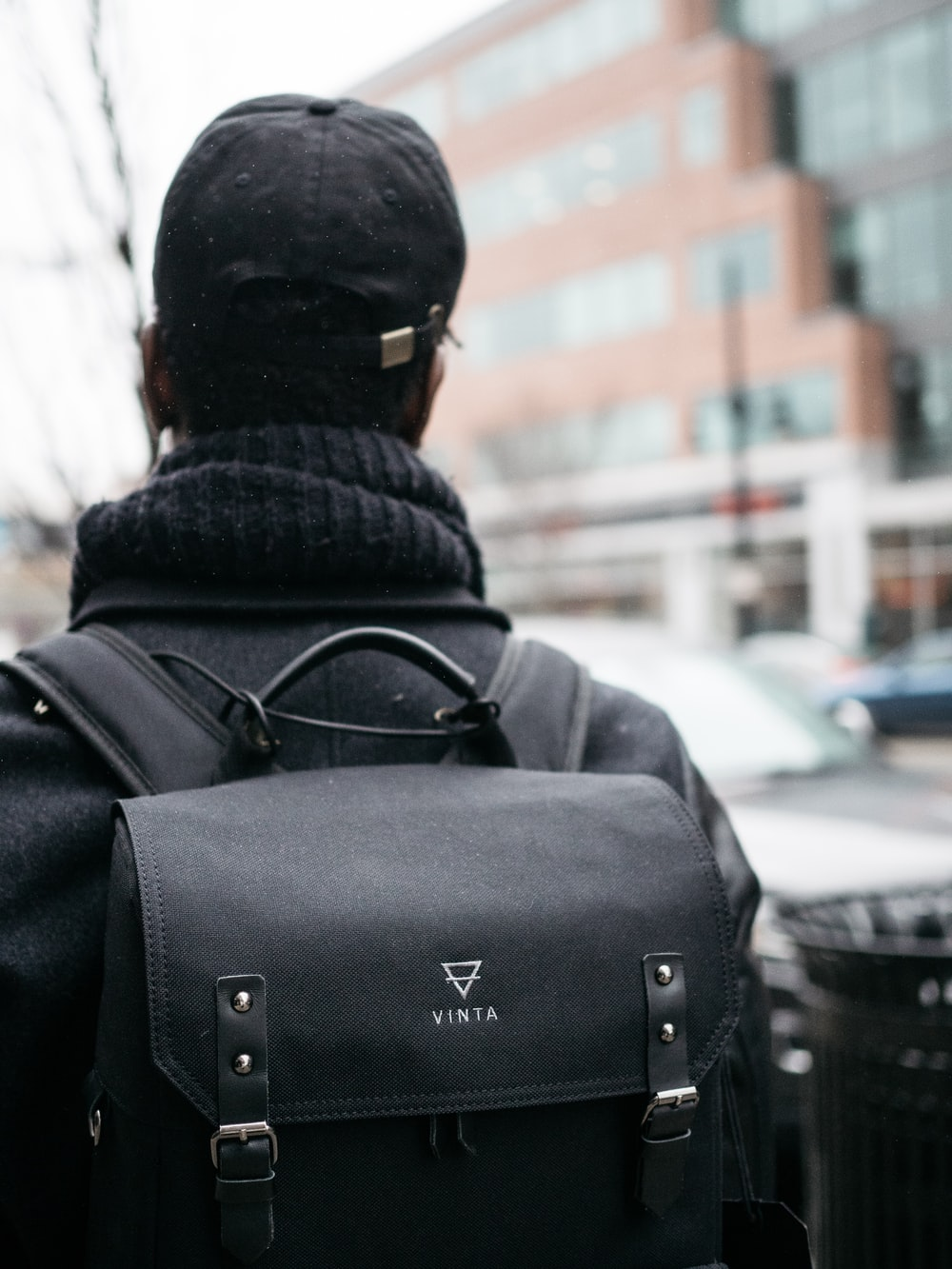 man wearing black top. hat, and Vinta backpack selective focus photography