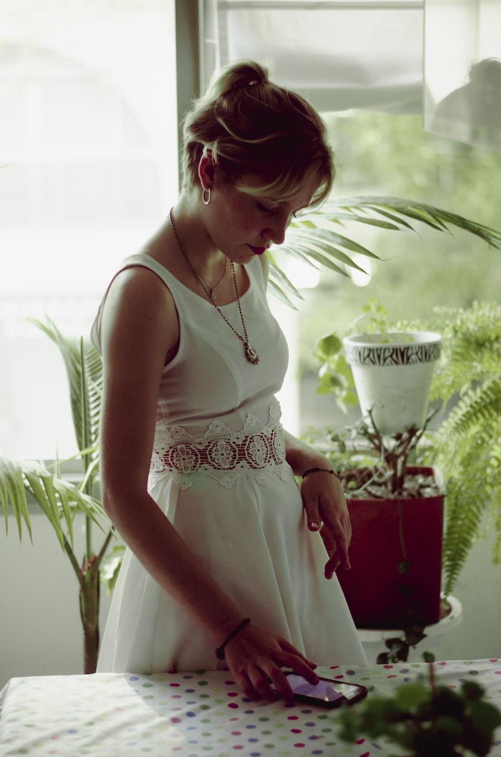 women's white sleeveless dress using smartphone on table