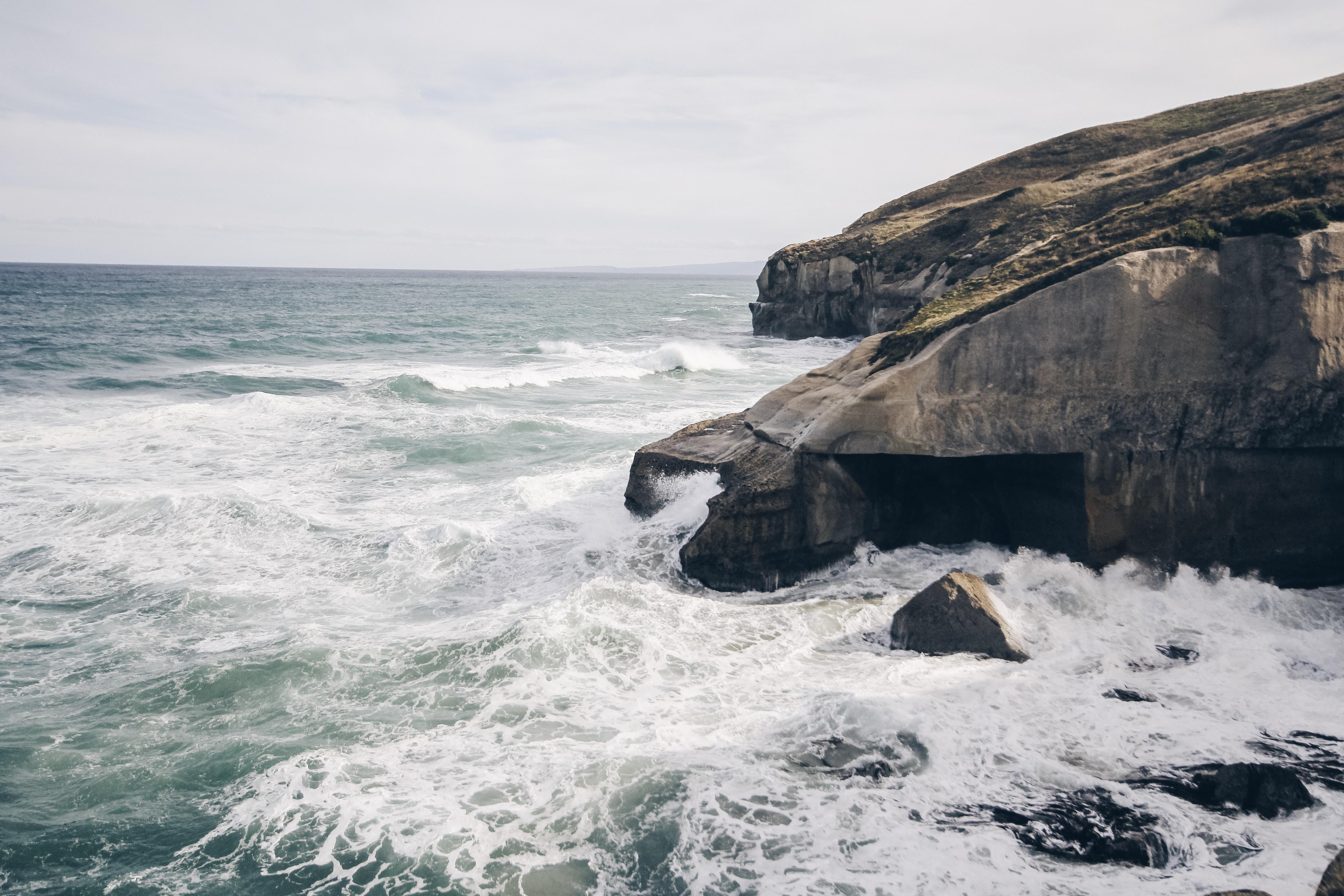 rock cliff beside body of watwer