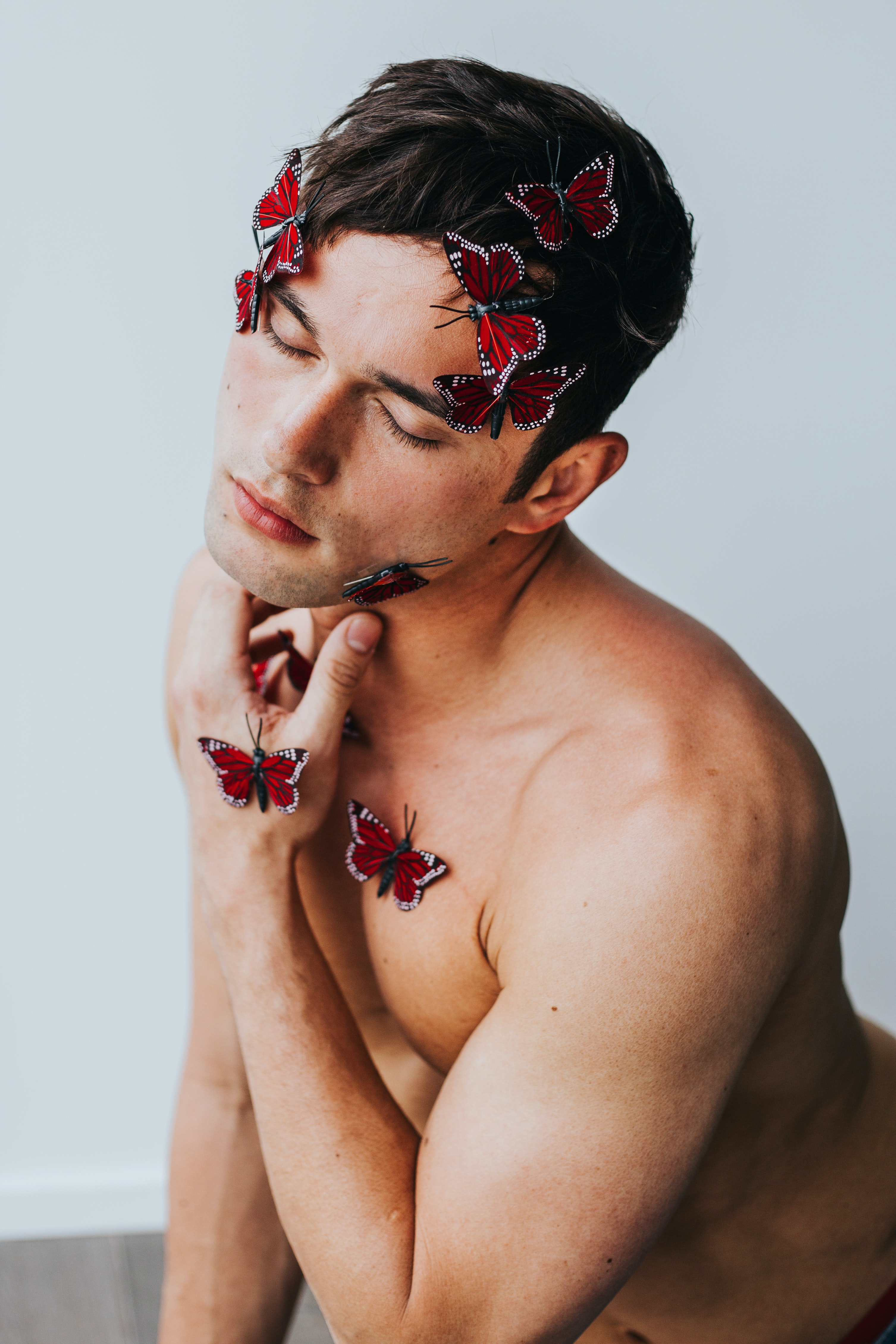 man covered with red butterflies