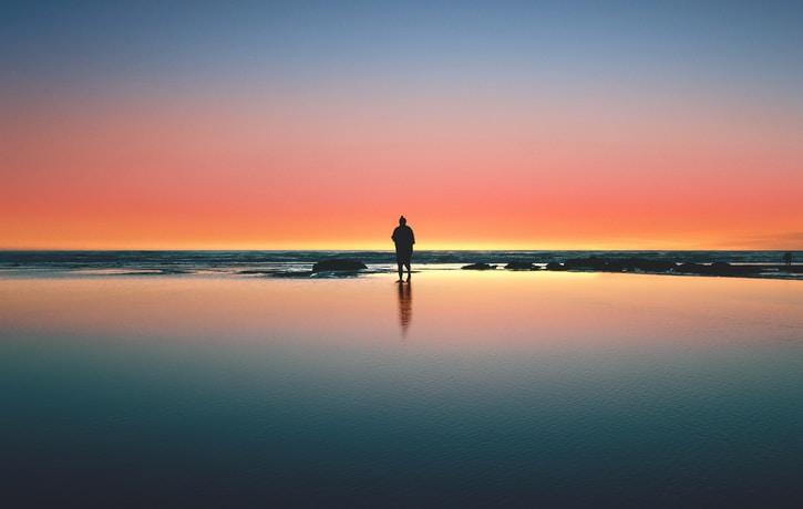 silhouette of man standing on seashore