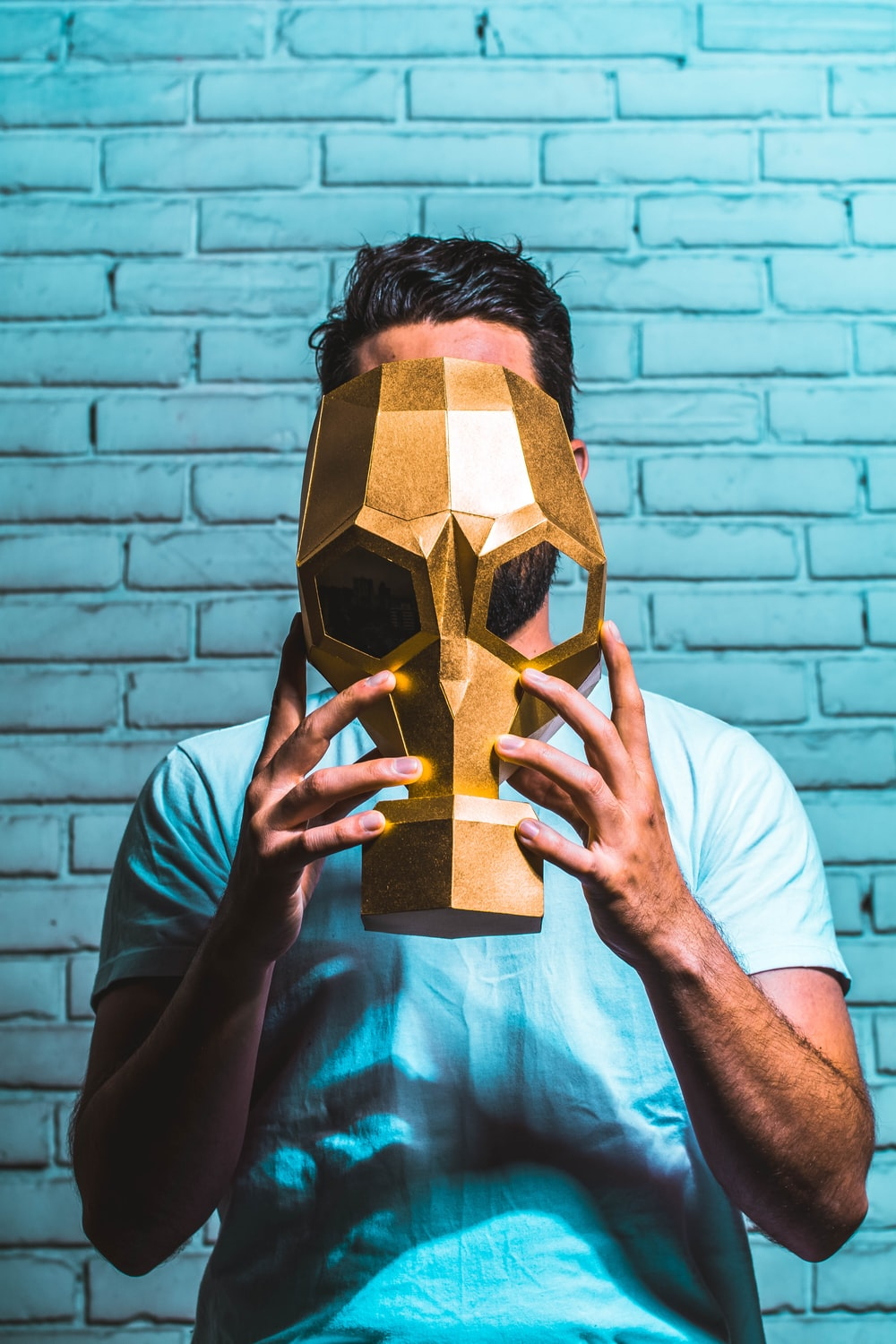 man holding a mask with gold paint