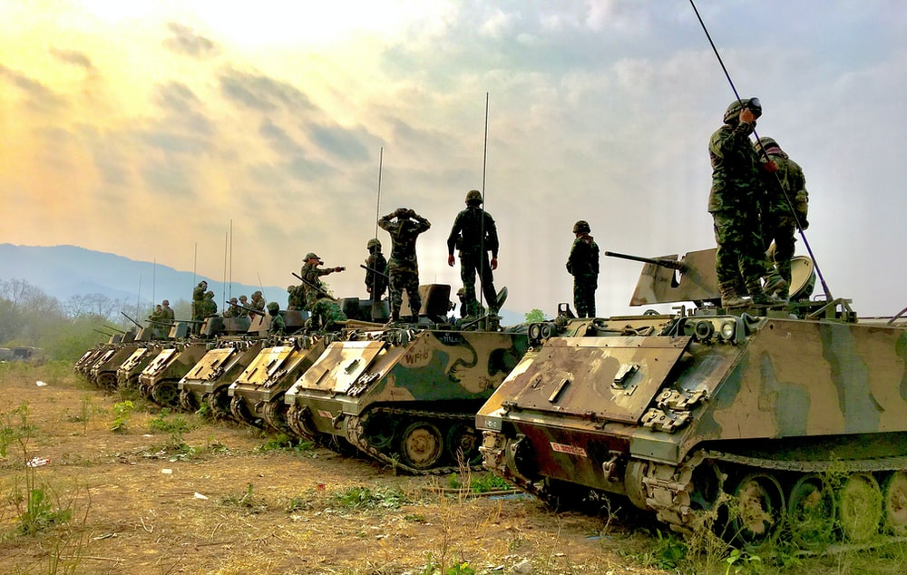 soldiers on top of battle tanks