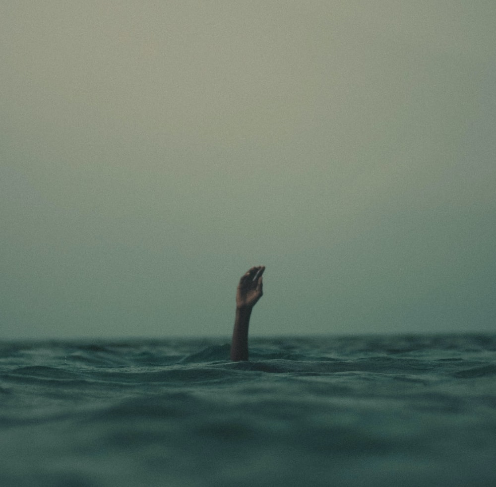 person with hand above water