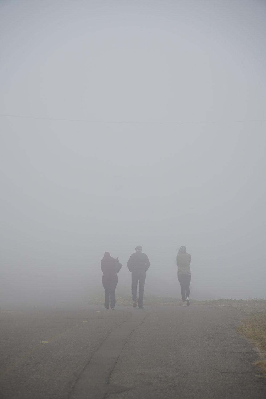 three people walking on dirt trail