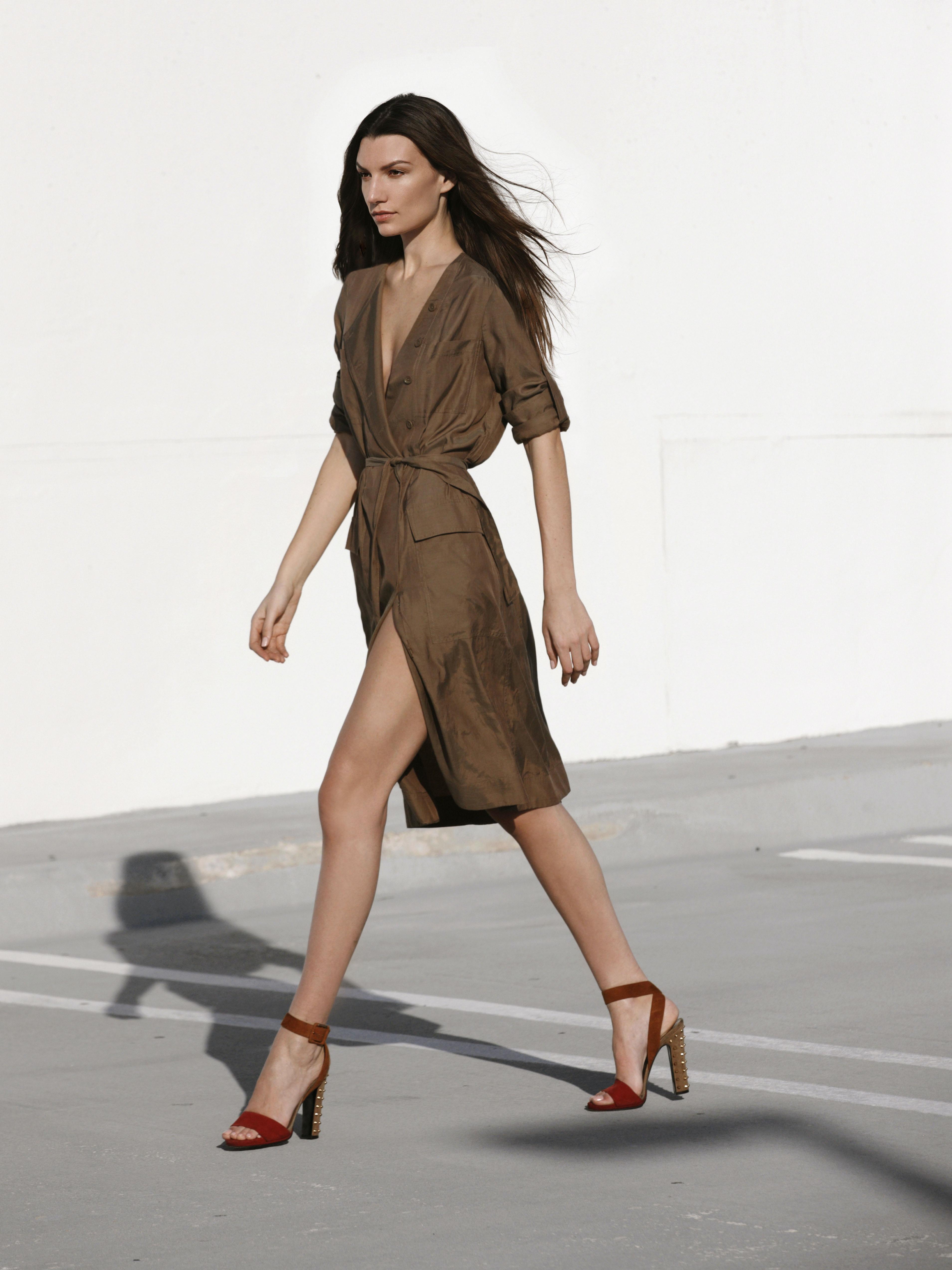 woman in brown dress walking on gray asphalt road