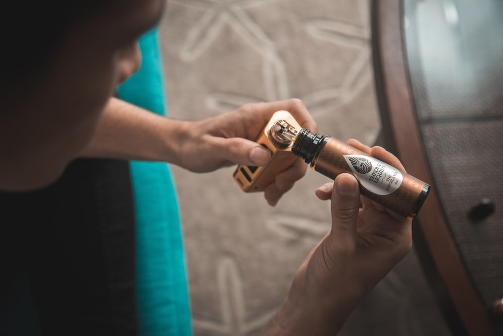 person putting e-juice on gold Wismec variable vaporizer