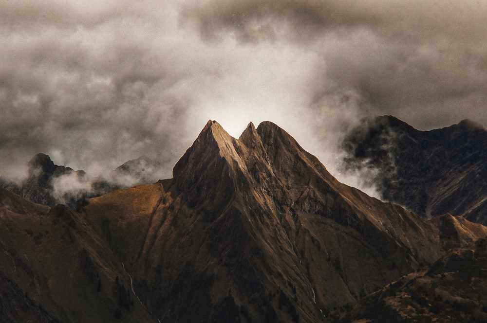 brown mountain with clouds