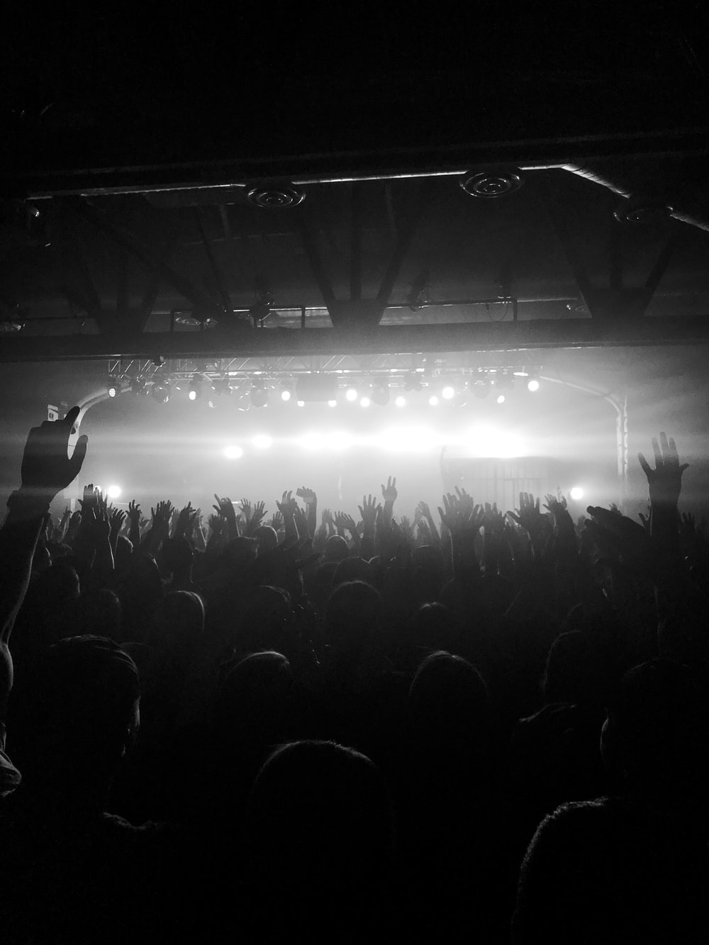 grayscale photo of people raising hands