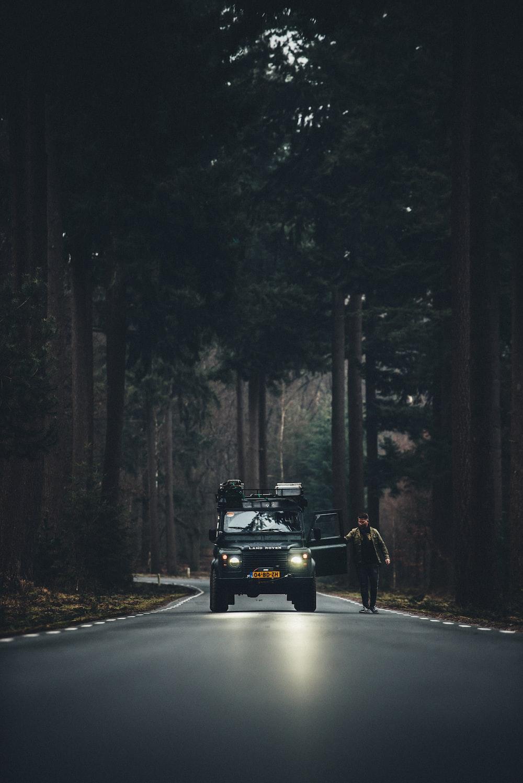 man in brown jacket standing beside car on road