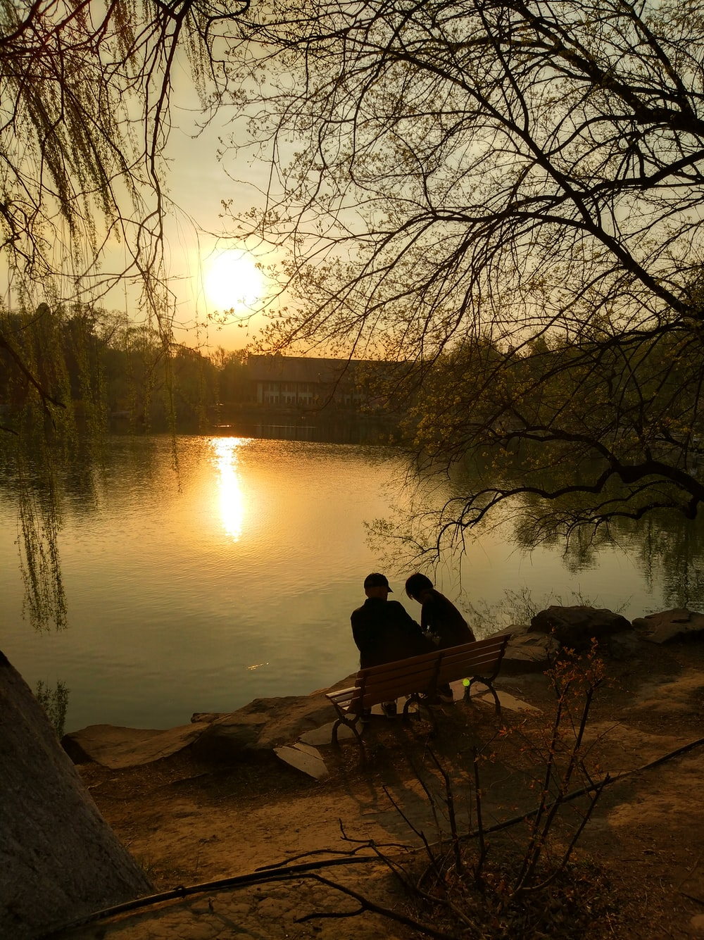 two person sitting on bench near lake