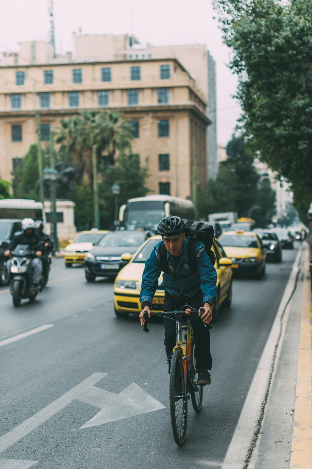 man riding bicycle on a road with cars during daytime
