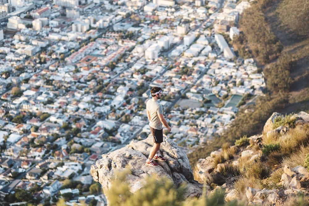 man standing near mountain cliff