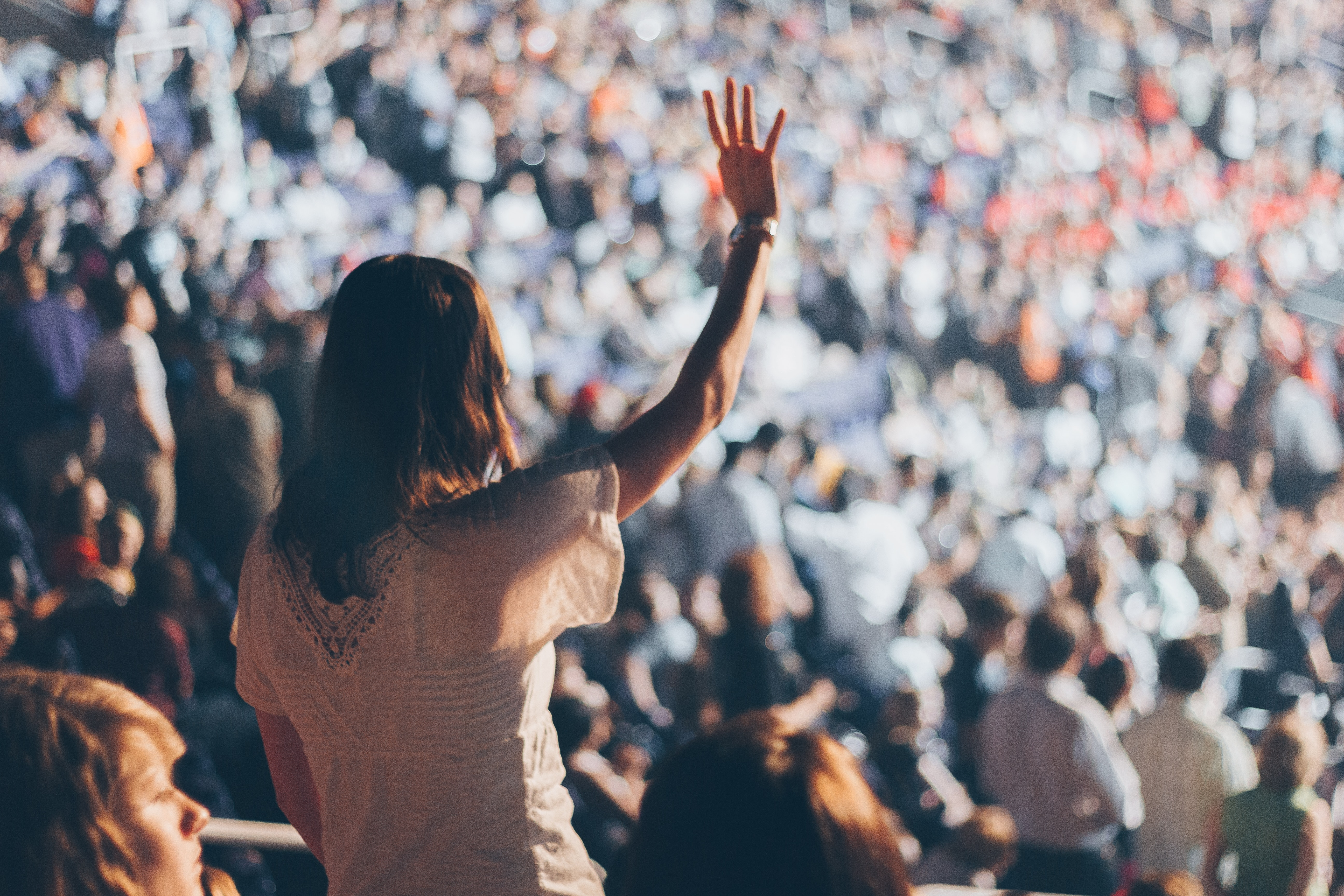 woman in white shirt raising her right hand