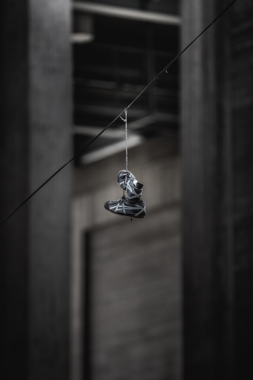 pair of black-and-gray ASICS shoes hanging on wire