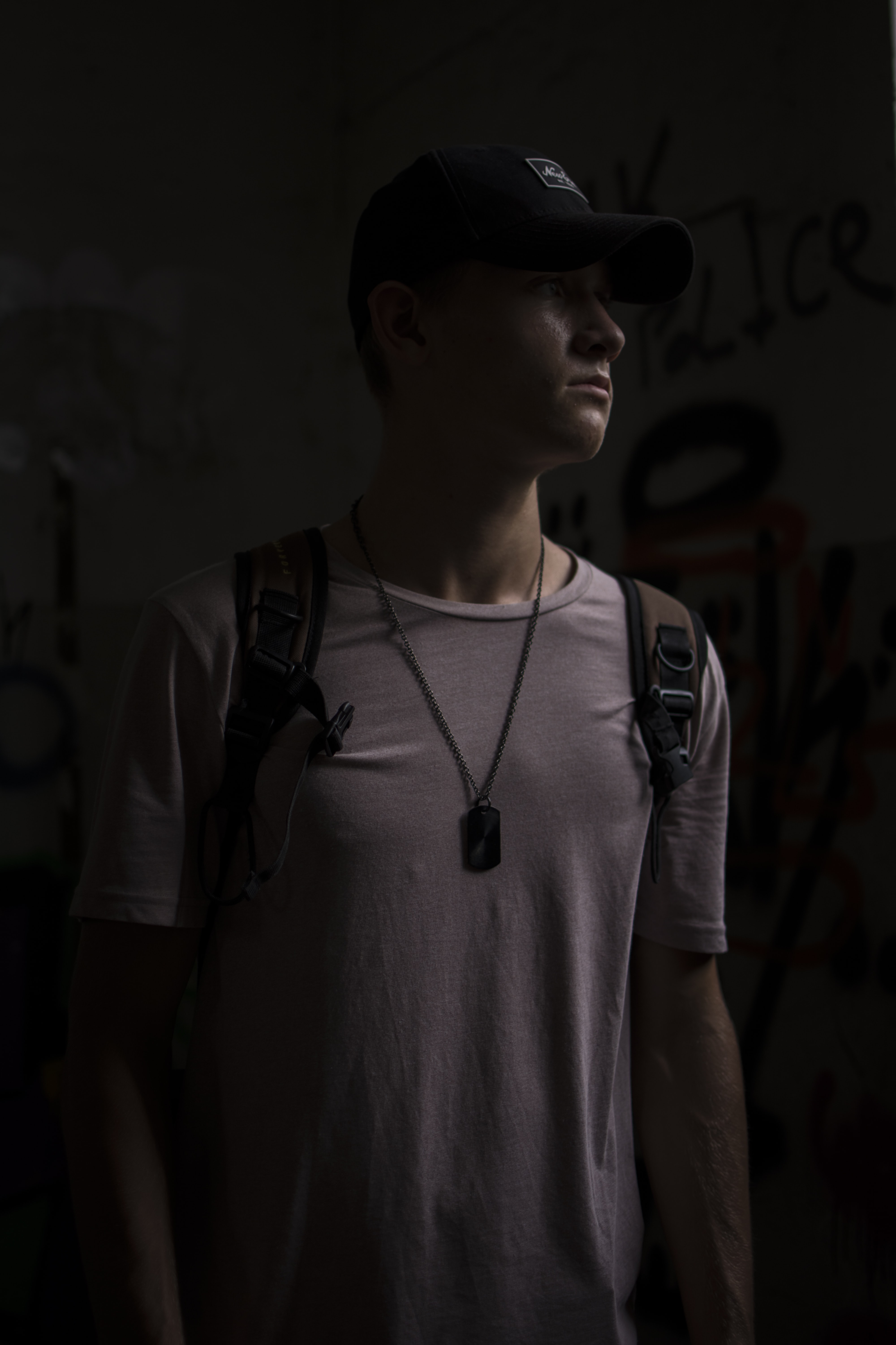 man wearing white T-shirt and backpack standing in a dark lit room