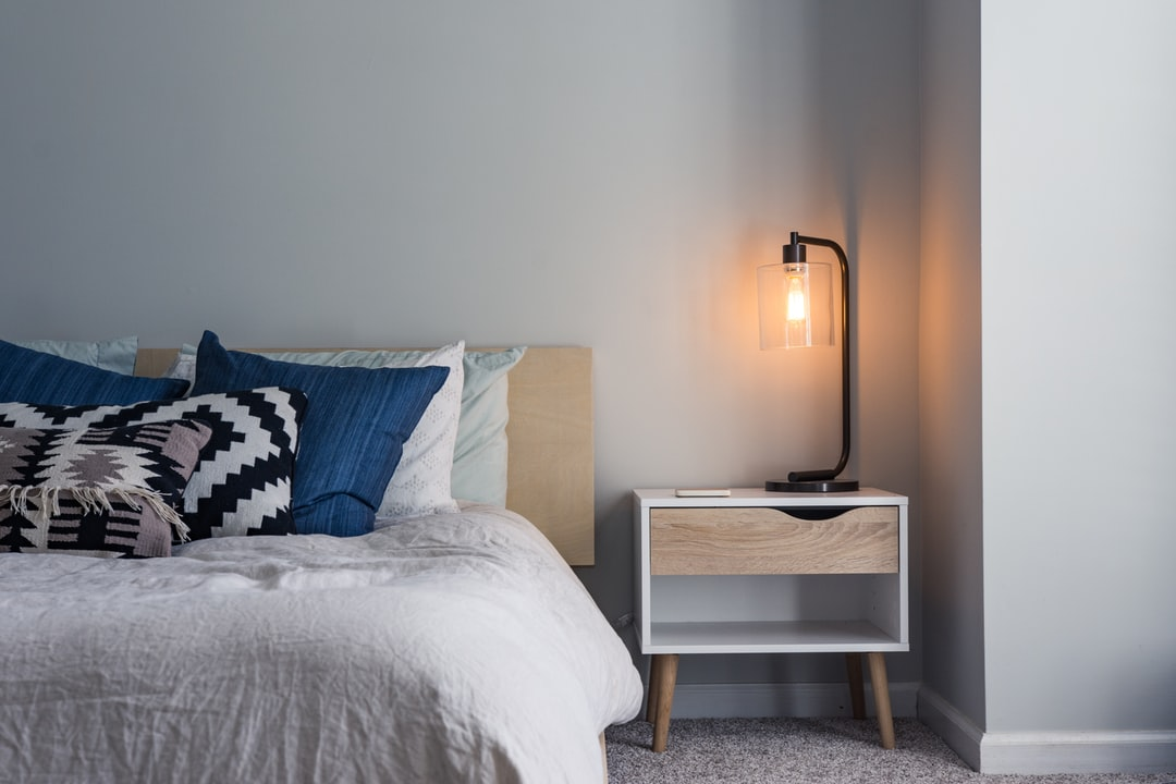 A double bed scattered with pillows and a bedside table with a black modern lamp