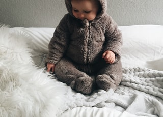 baby seating on white textile