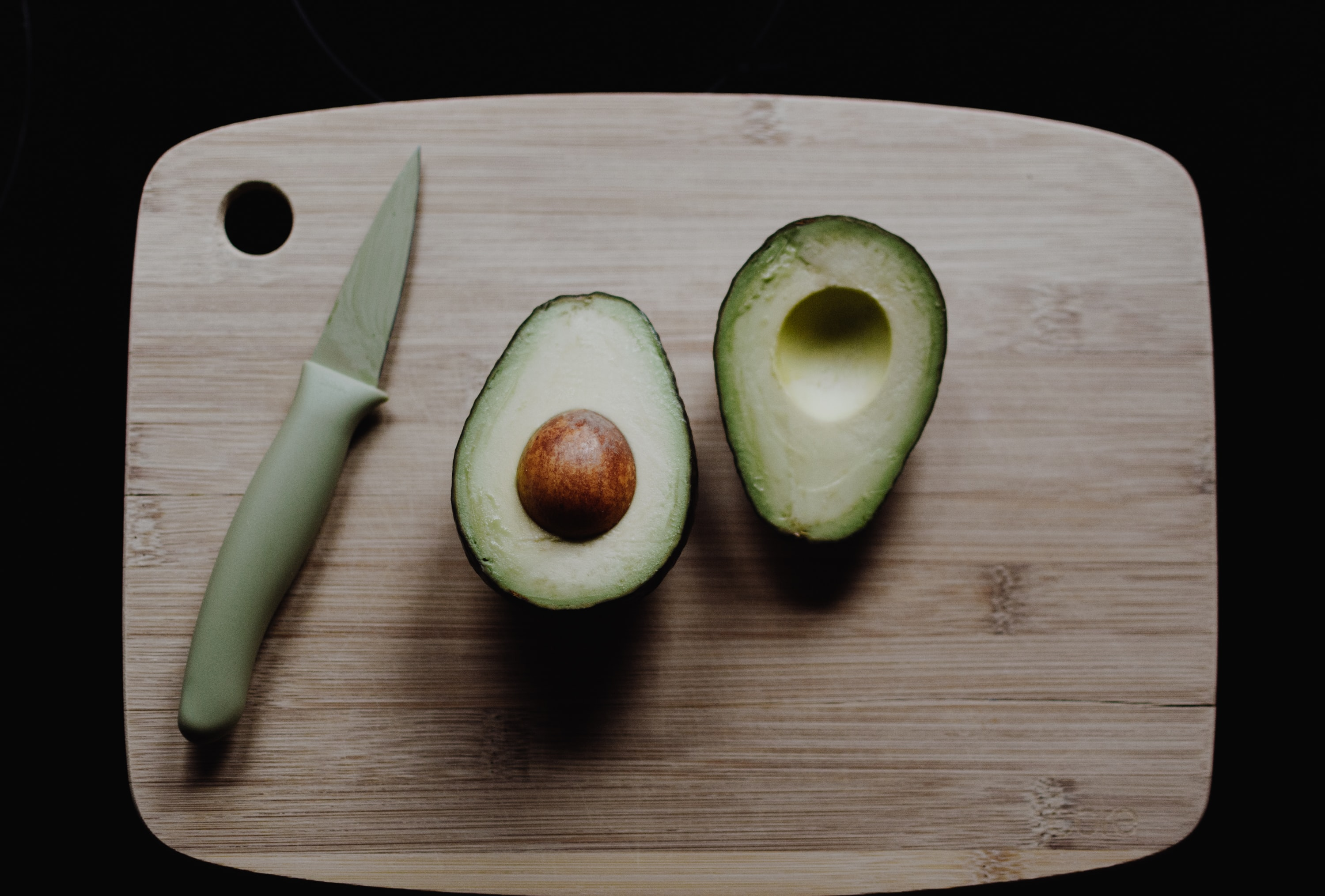 sliced avocados on top of brown wooden chopping board in top view photography