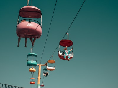 people on assorted-color cable cars at daytime retro zoom background