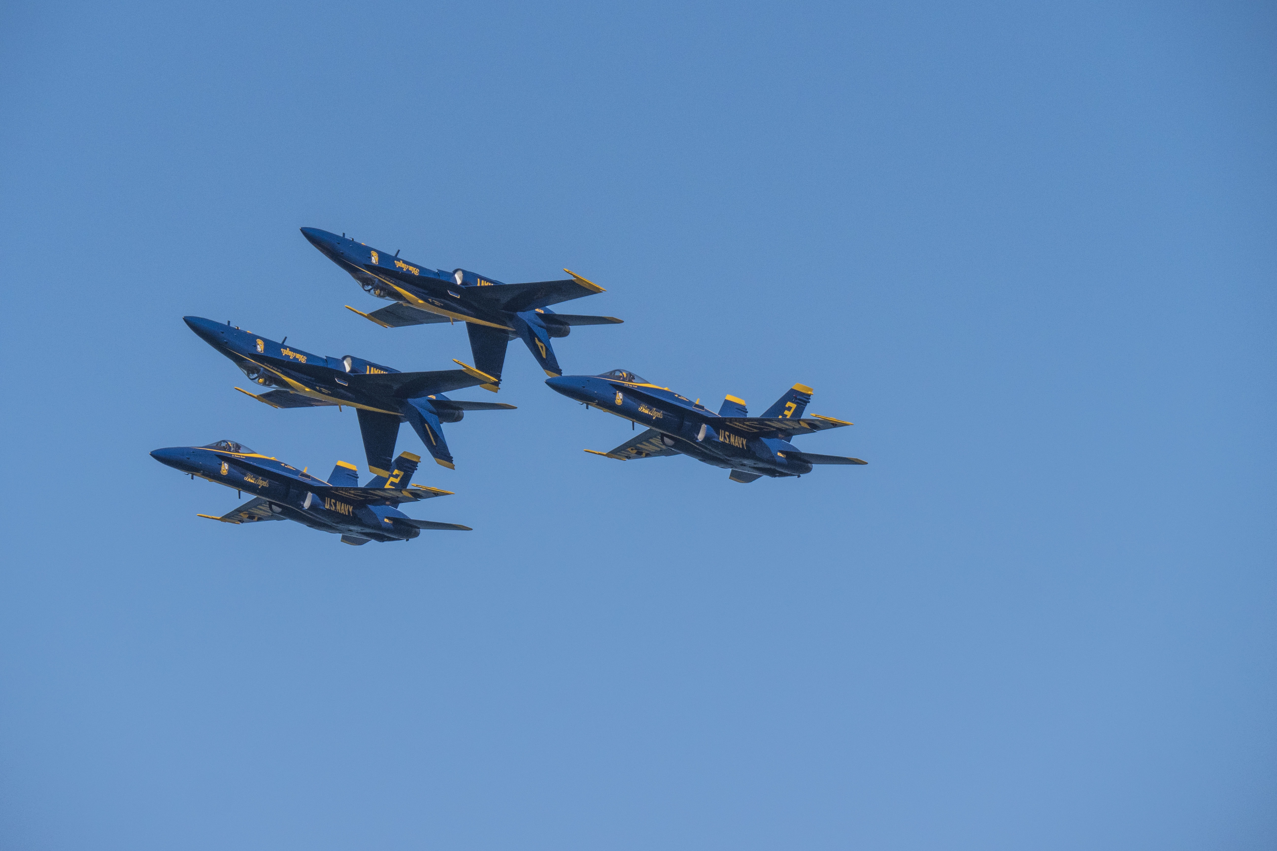 four blue-and-yellow aircrafts performing air show trick