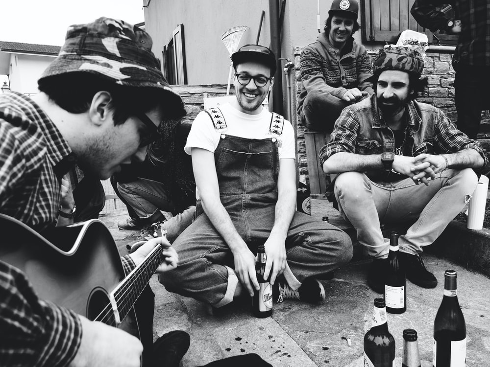 grayscale photo of people singing while drinking