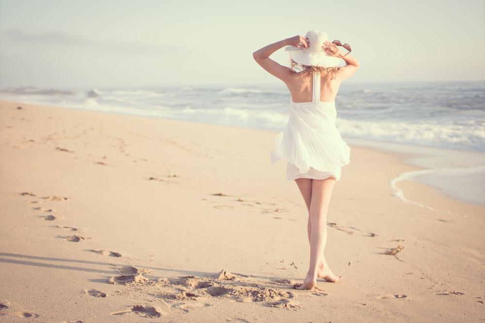 woman walking on beach during daytime