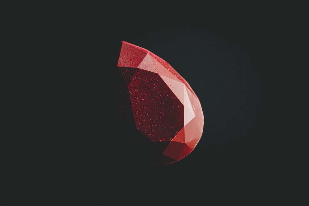 selective focus photography of faceted red gemstone