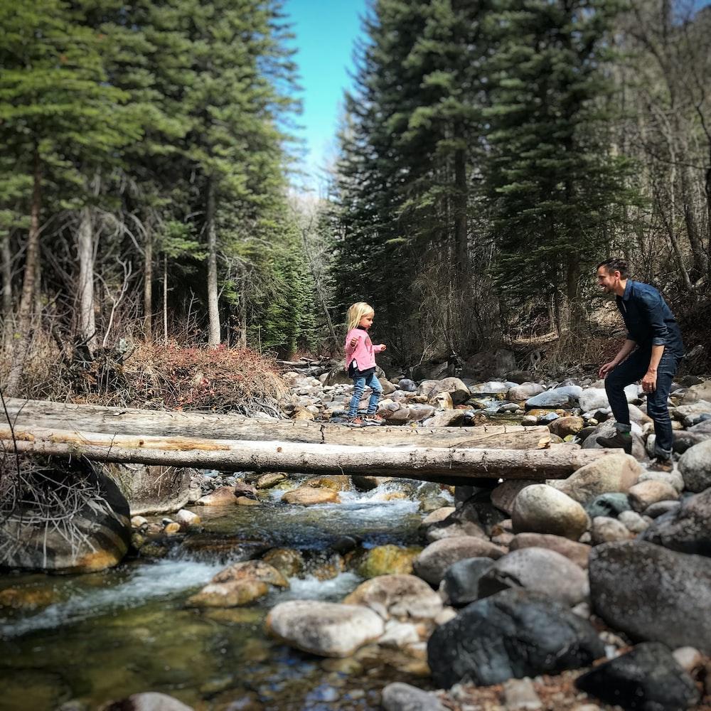 girl crossing wood lumber bridge