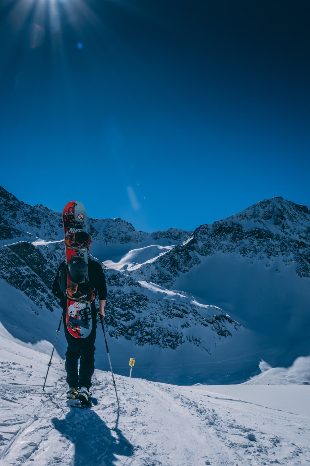 person standing on mountains with snow during daytime
